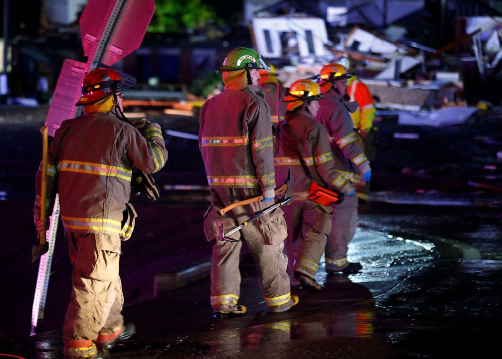 PHOTO: Firefighters walk to an area of debris from a hotel and a mobile home park in El Reno, Okla., May 26, 2019, following a tornado.