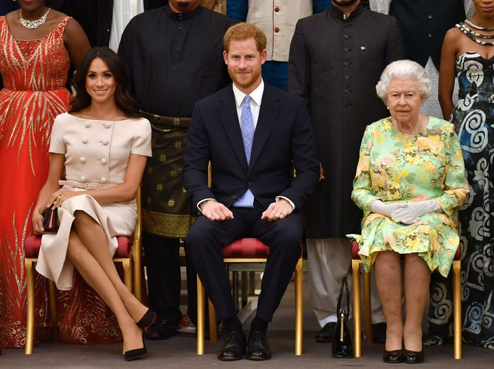Meghan, Duchess of Sussex, Prince Harry and Queen Elizabeth II pose for a picture with some of Queen's Young Leaders at a Buc